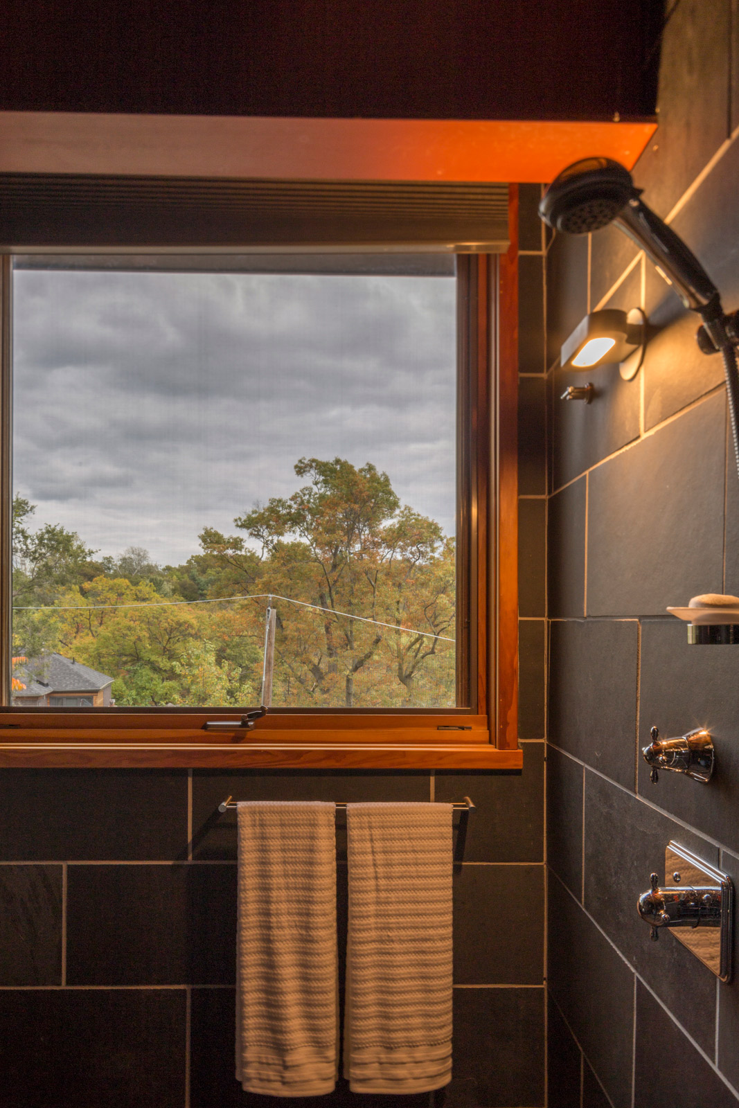 The open shower is tiled with slate and has expansive views down to Toronto's High Park