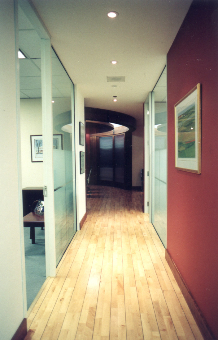 Office hallway with partial glass wall, and wood flooring