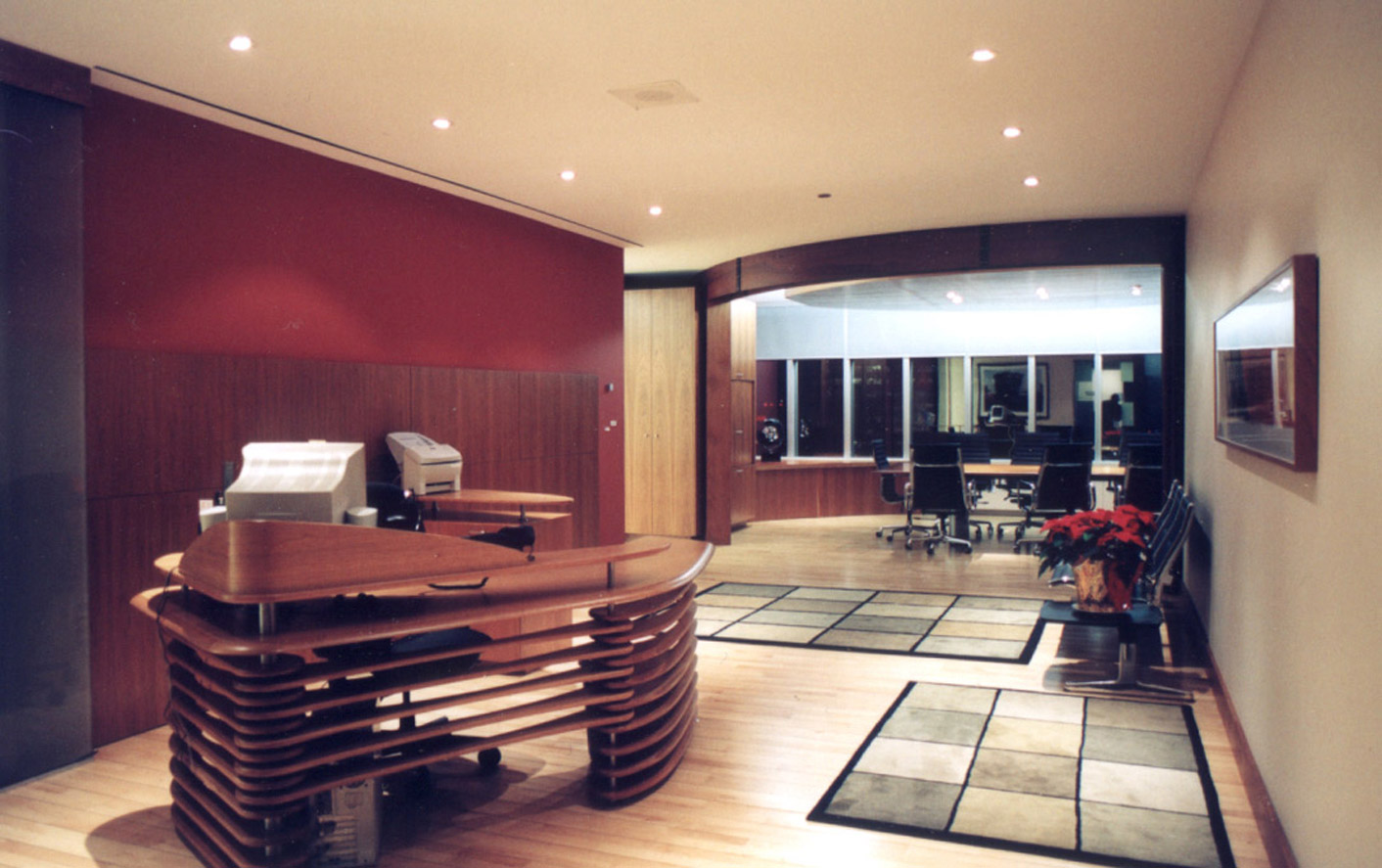 Office entrance with custom built reception desk and meeting room with large sliding doors