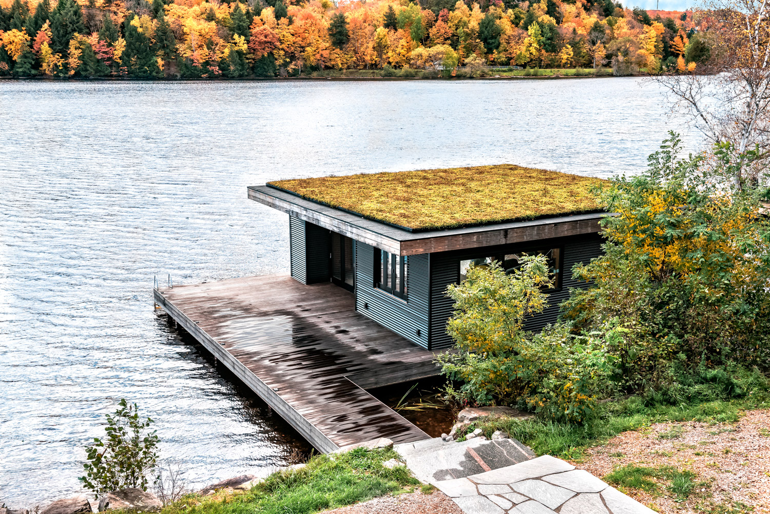 Muskoka boathouse with green roof corrugated steel siding and Kebony decking dock