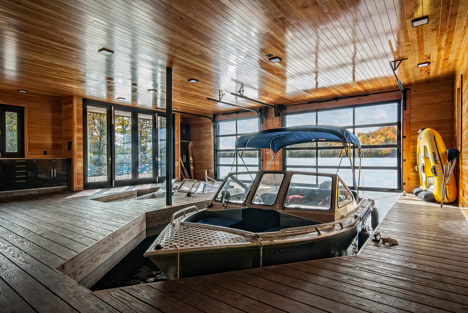 Interior of Muskoka Ontario boathouse with colour matched poplar on ceiling and walls and Kebony docks