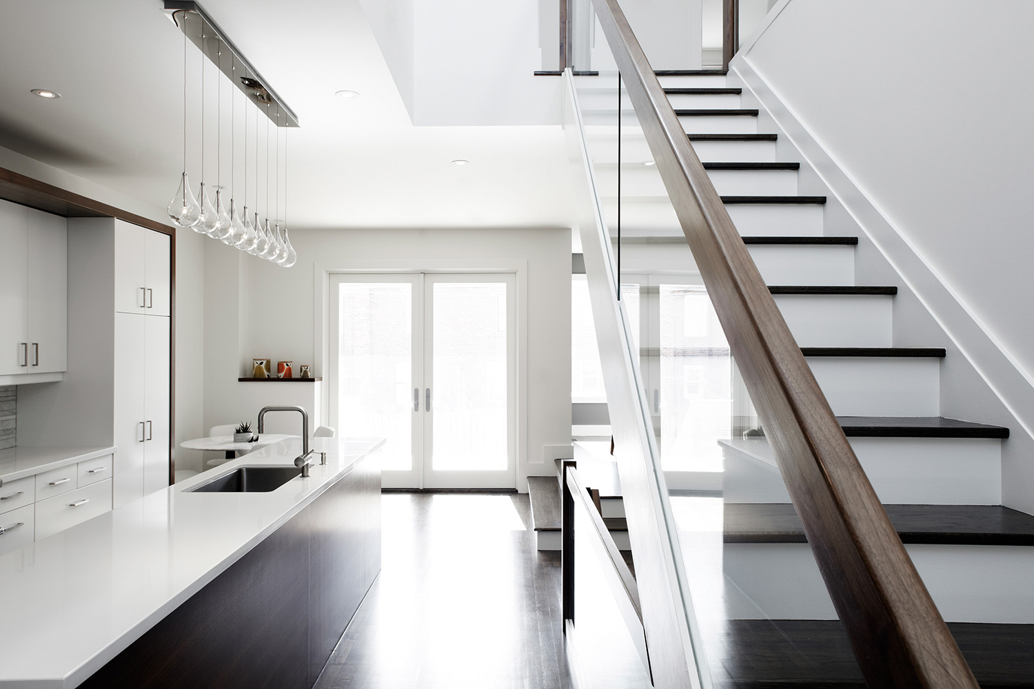 Open staircase with wood handrail open to kitchen with glass pendant light