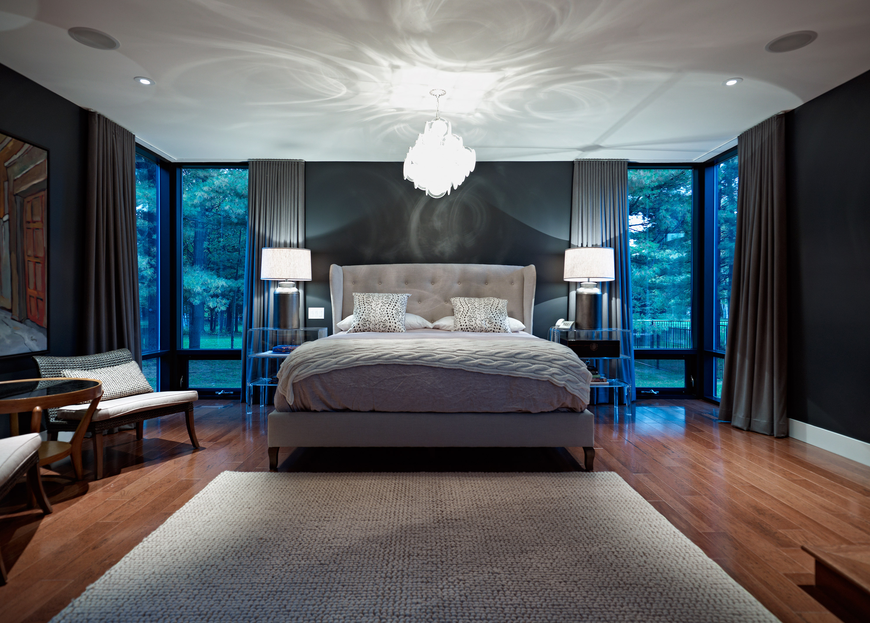 Master bedroom with corner windows, lounge seating and decorative hanging glass chandelier