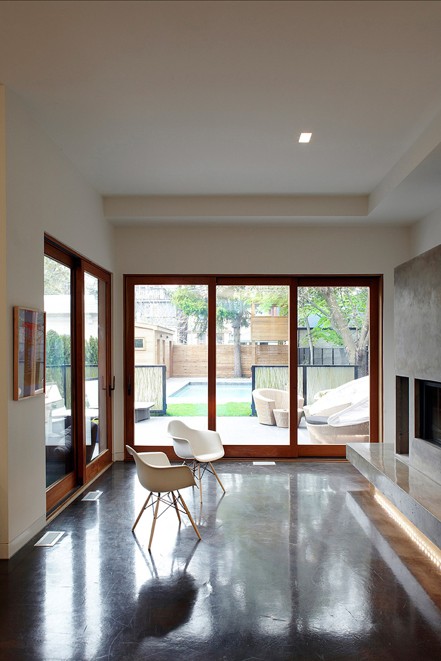 Siting Room with polished concrete floors, multi-panel sliding doors and fireplace placed in a concrete mantel