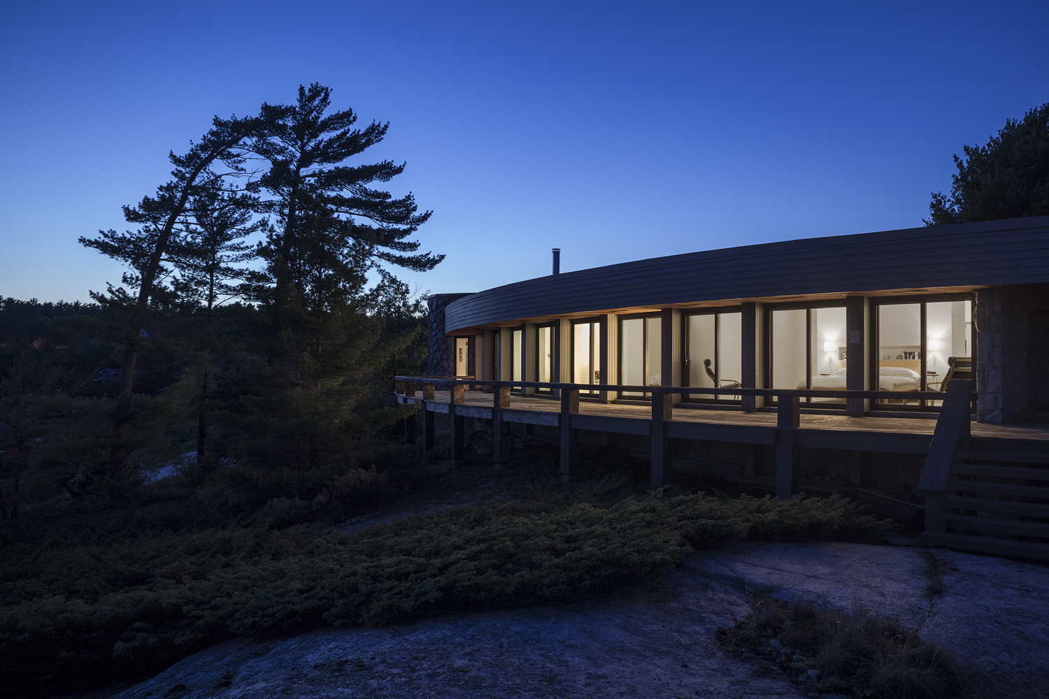 Curved Georgian Bay cottage with expansive views to the water made from natural wood materials
