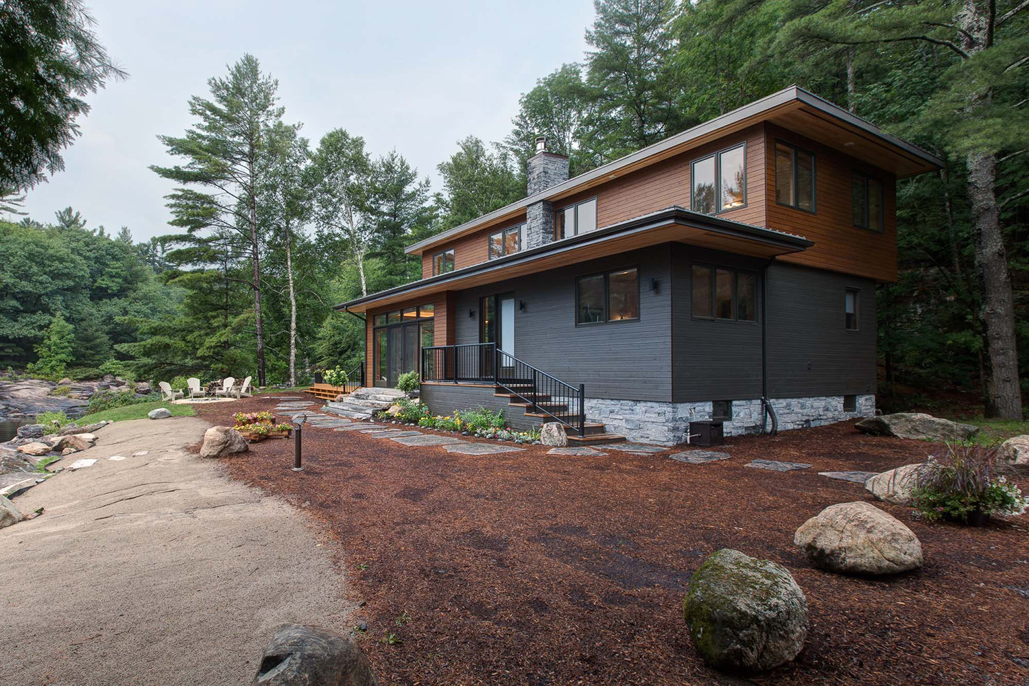 Contemporary Lake Rousseau cottage with exterior landscaping and campfire pit with Adirondack chairs