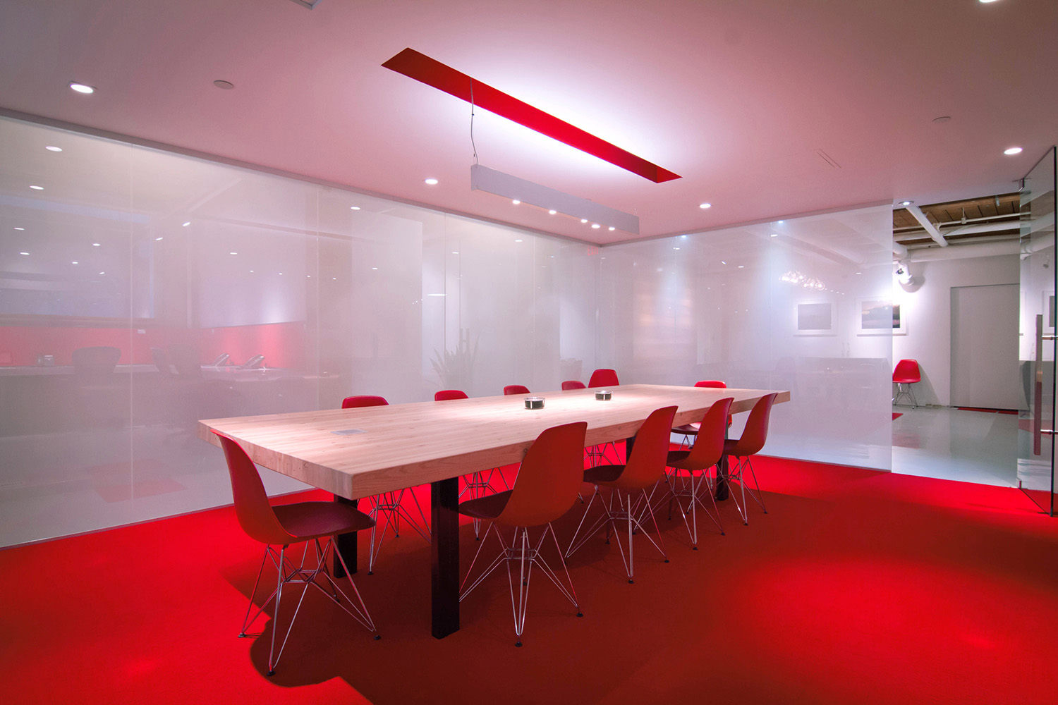Office boardroom with laminated wood meeting table and Milk Glass walls