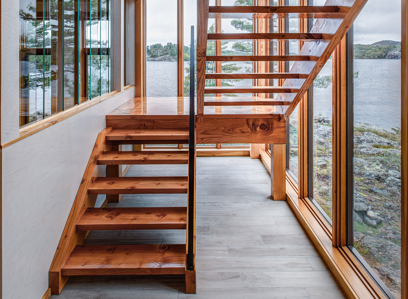 Custom built in place Douglas fir staircase, wood interior curtain wall, offset glass panel wall