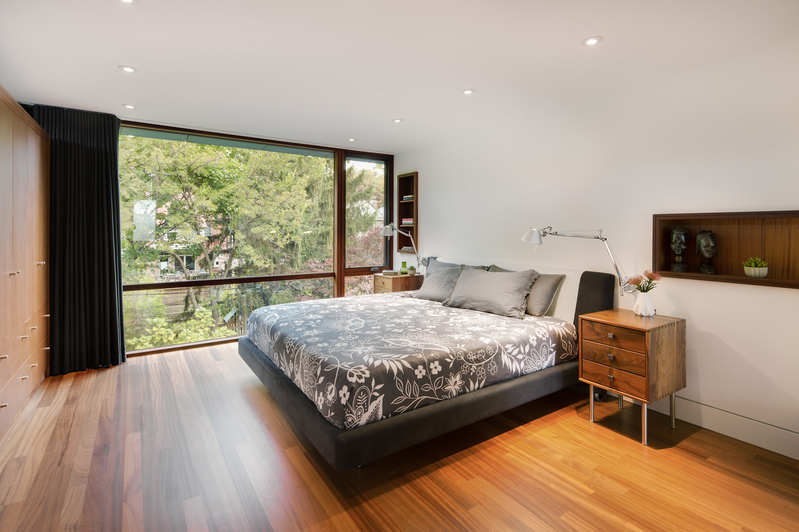 Master bedroom with view of Roncevalle neighbourhood with integrated wood shelving and full wall wood built in wardrobe