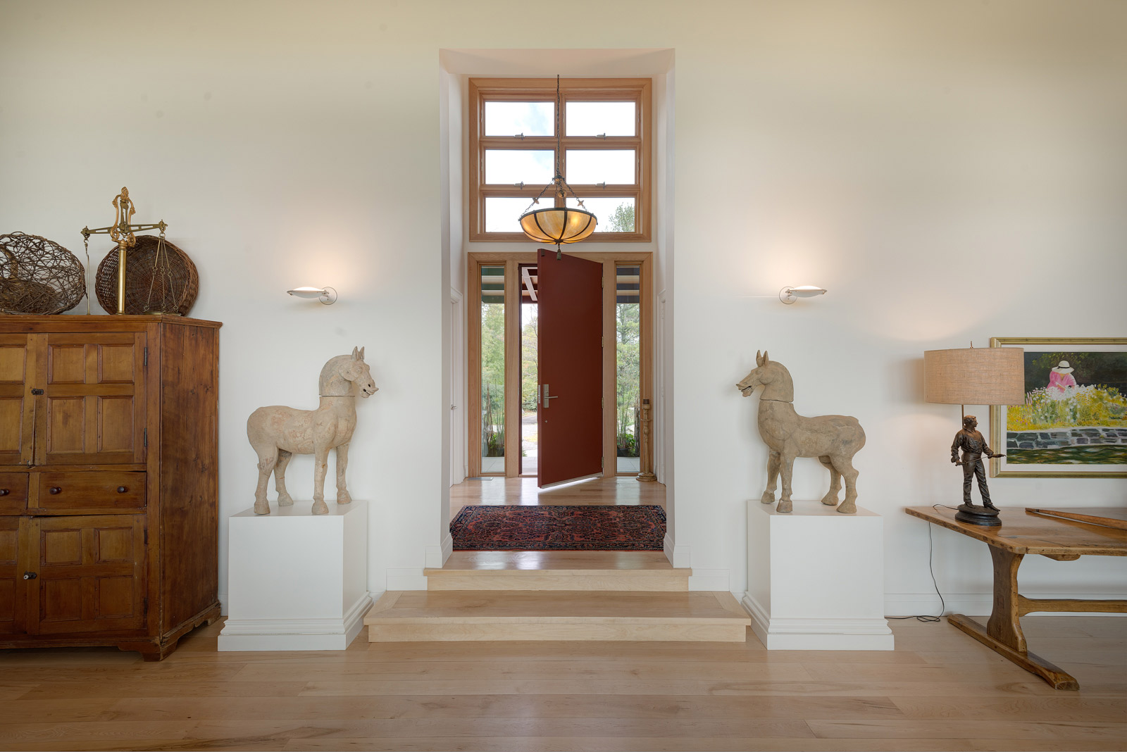 Entryway with large main door with sidelights and transom windows. Clean maple floors and small stair to great room