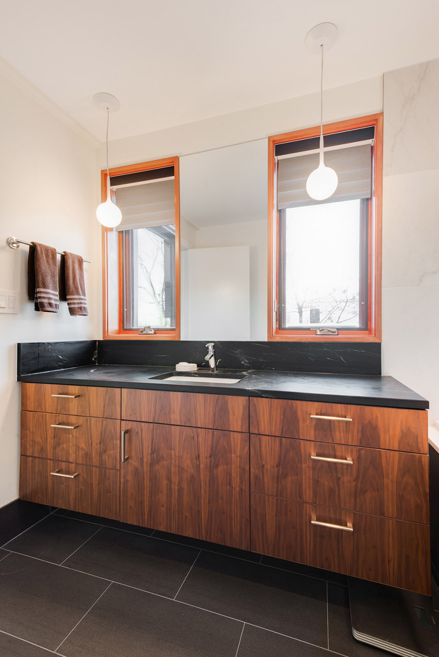 Bathroom with wood vanity and black marble countertop stainless steel fixtures and pendant lights