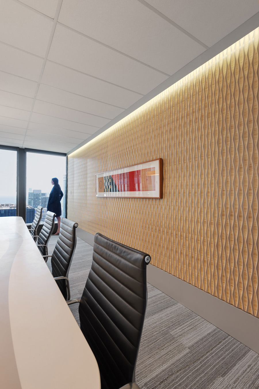 Modern office boardroom, with recessed lighting and textured accent wall