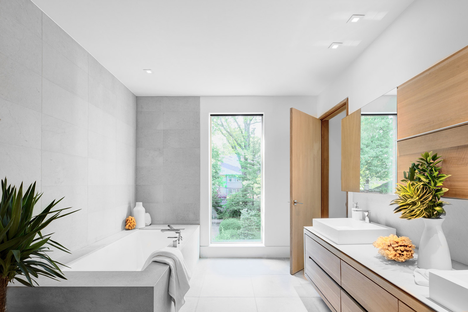 Master Bathroom with large integral soaking tub with muted gray tiles and basin sinks