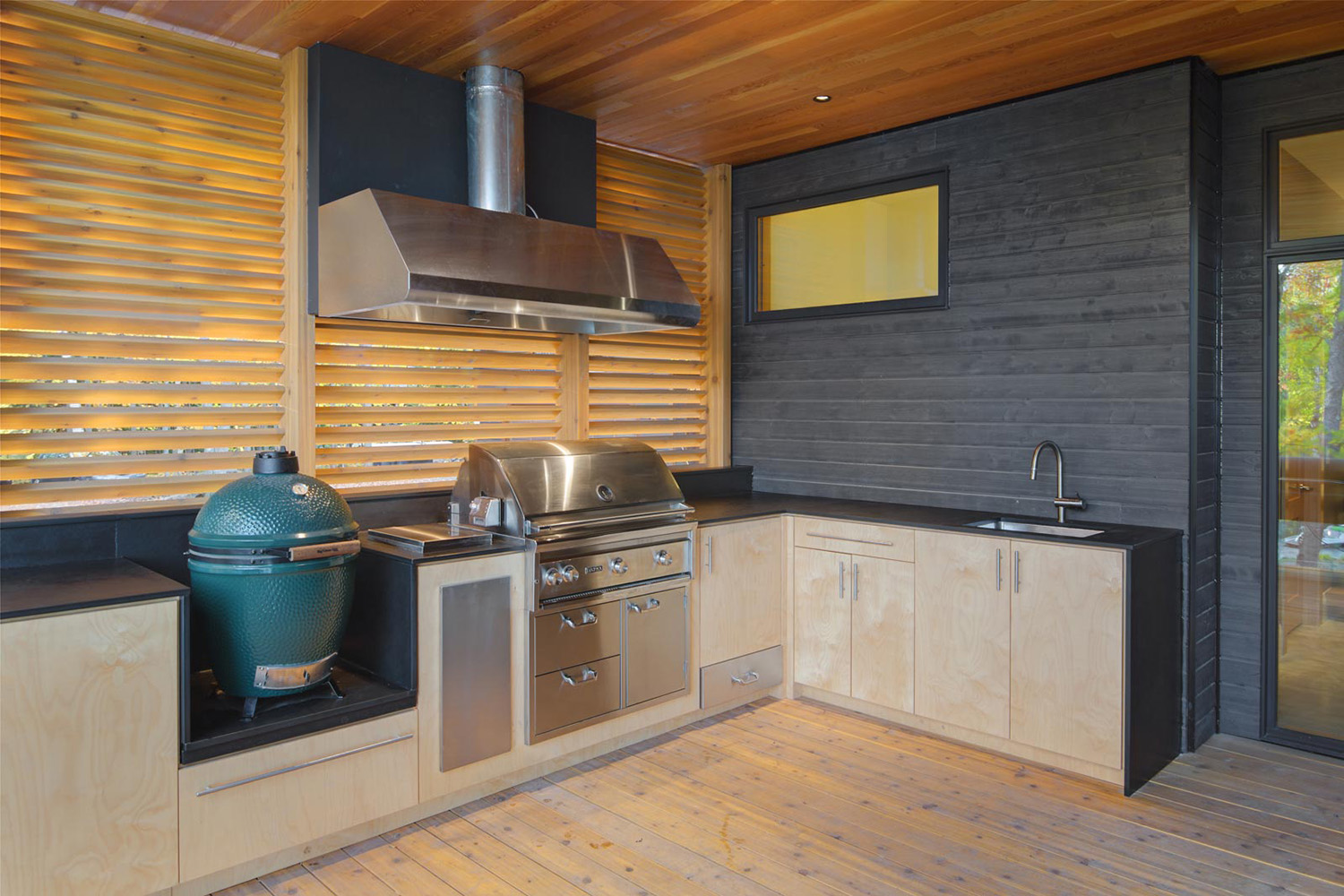 Exterior kitchen with integral BBQ and charcoal smoker with vent hood, maple cabinetry with a wood slat brise-soleil
