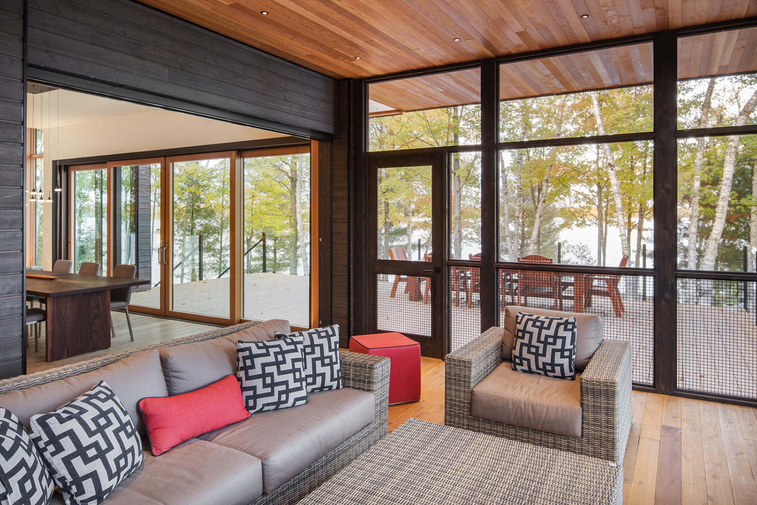 Sunroom with large sliding door access to main cottage with exterior furniture