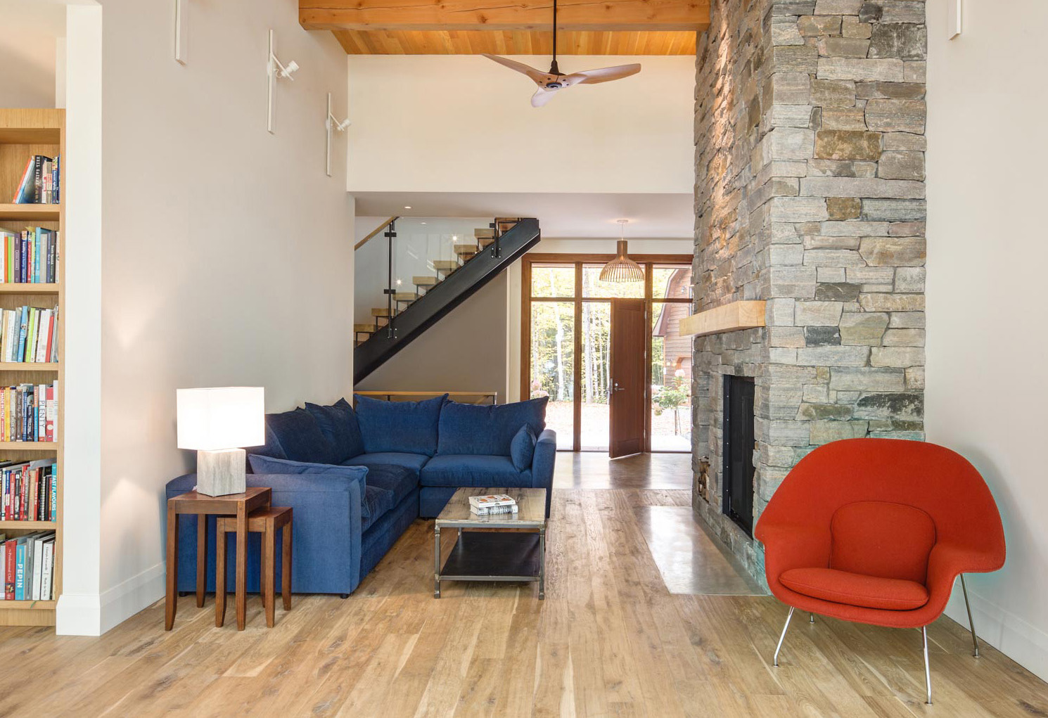 Seating area with stone fireplace with wood mantel sectional couch, and chair with a contemporary ceiling fan