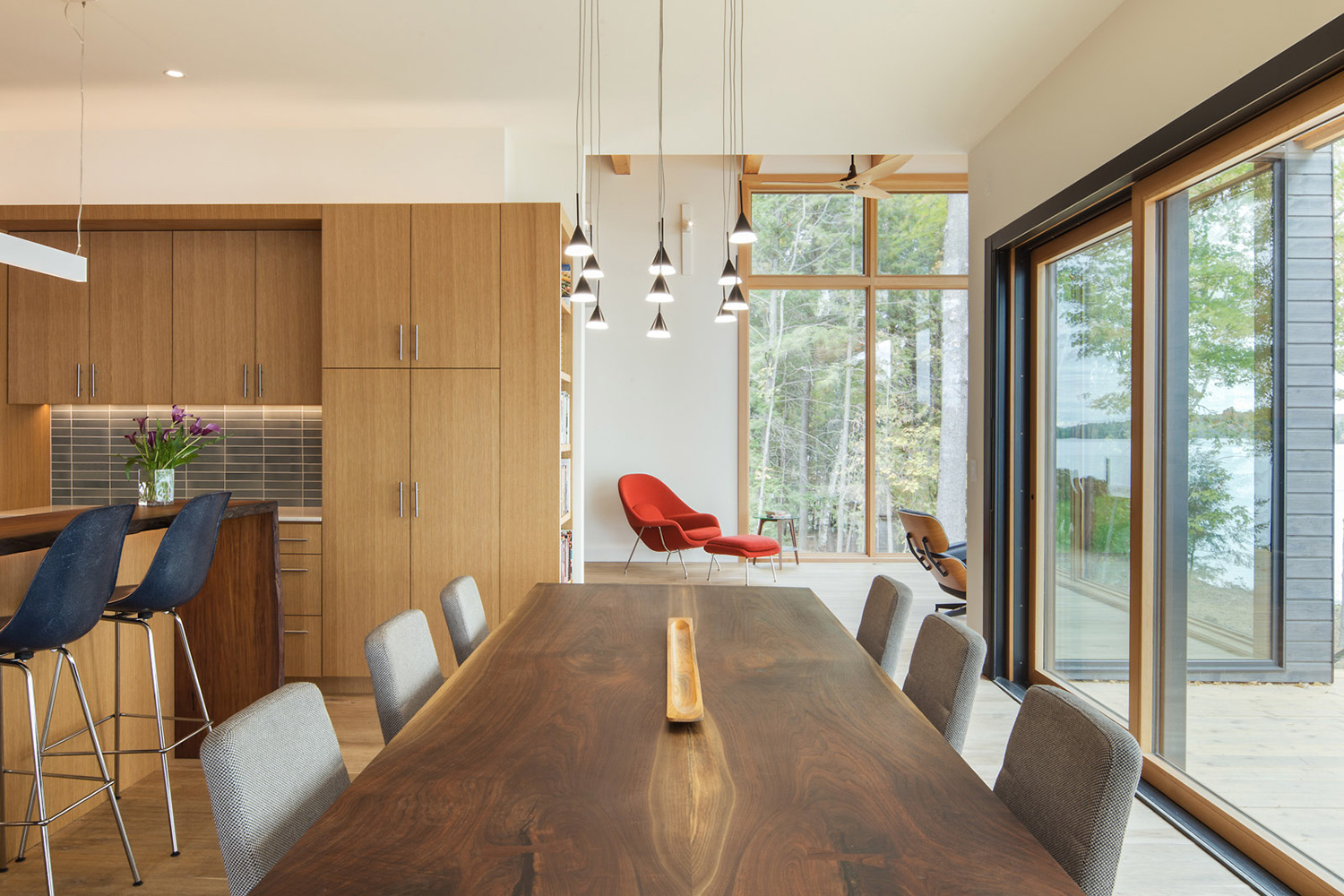 Dining room with large contemporary wood dining room table open to kitchen with pendant lighting