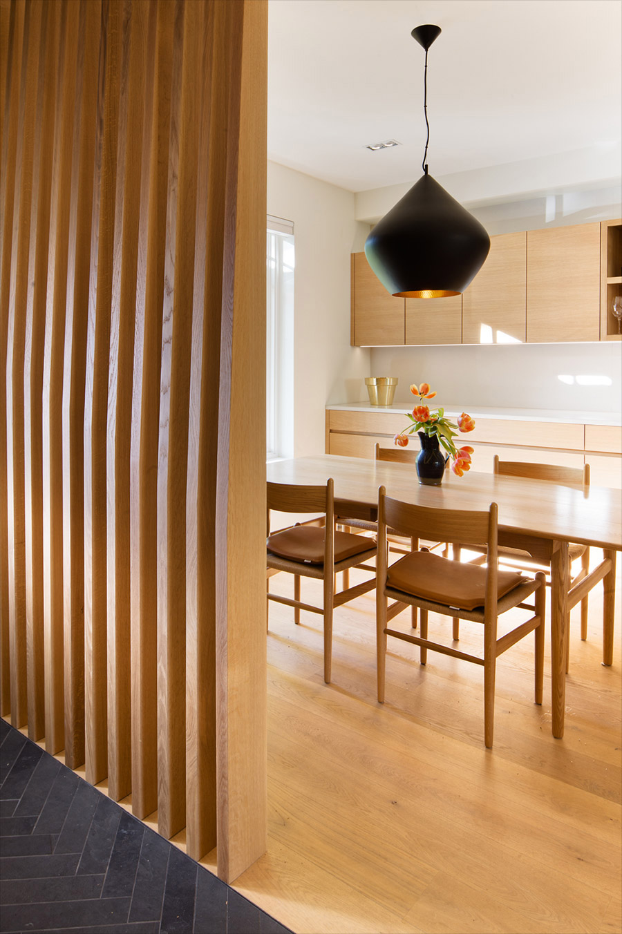 Dining room with modern white oak dining set with contemporary metal light fixture and white oak cabinetry