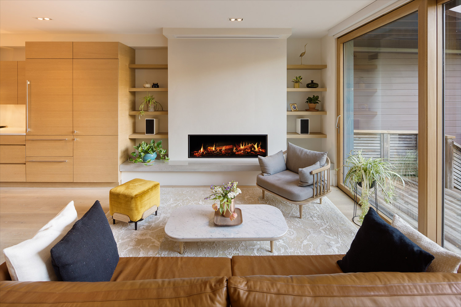 Living room with modern ribbon fireplace and full wall sliding door with white oak frame
