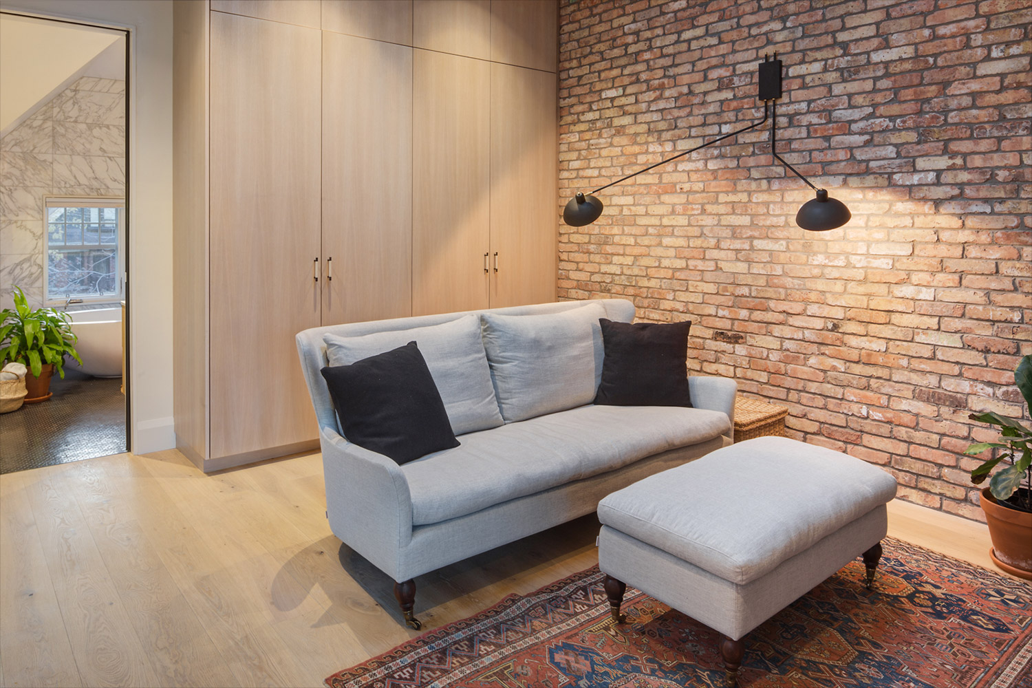 Siting room with exposed brick wall, white oak wardrobes and light gray sofa with ottoman
