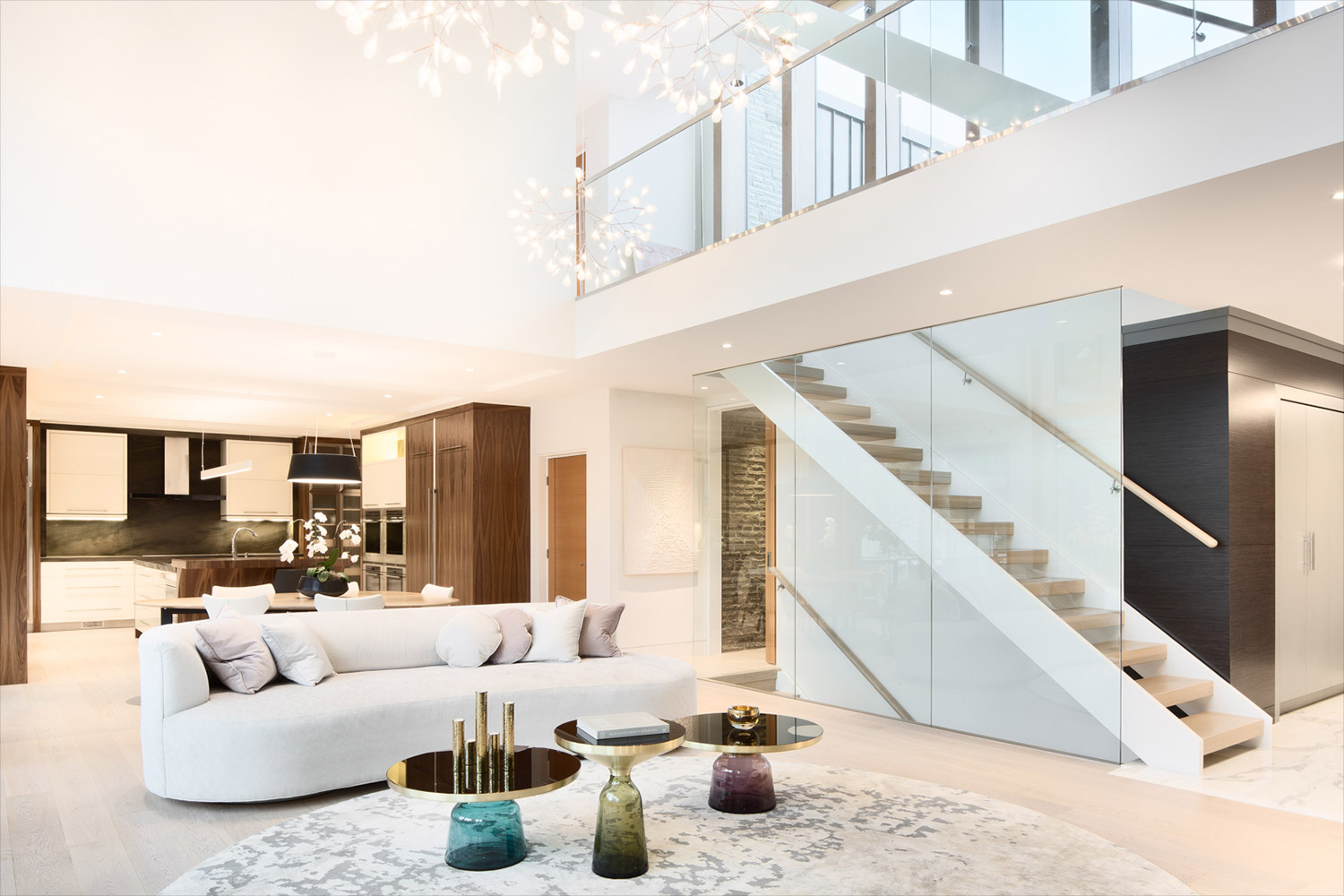 Double height living room of modern Toronto home with couch, wide plank flooring, and sculptural chandeliers