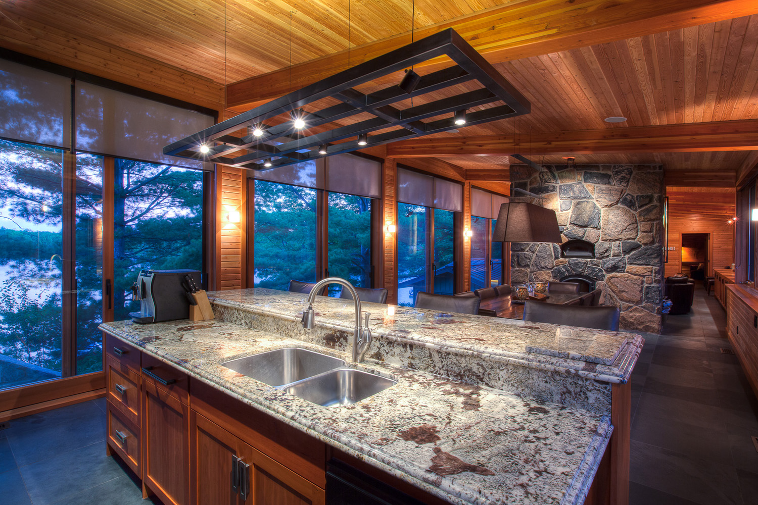 Cottage kitchen with monumental stone fireplace, granite countertops and engineered wood exposed structure