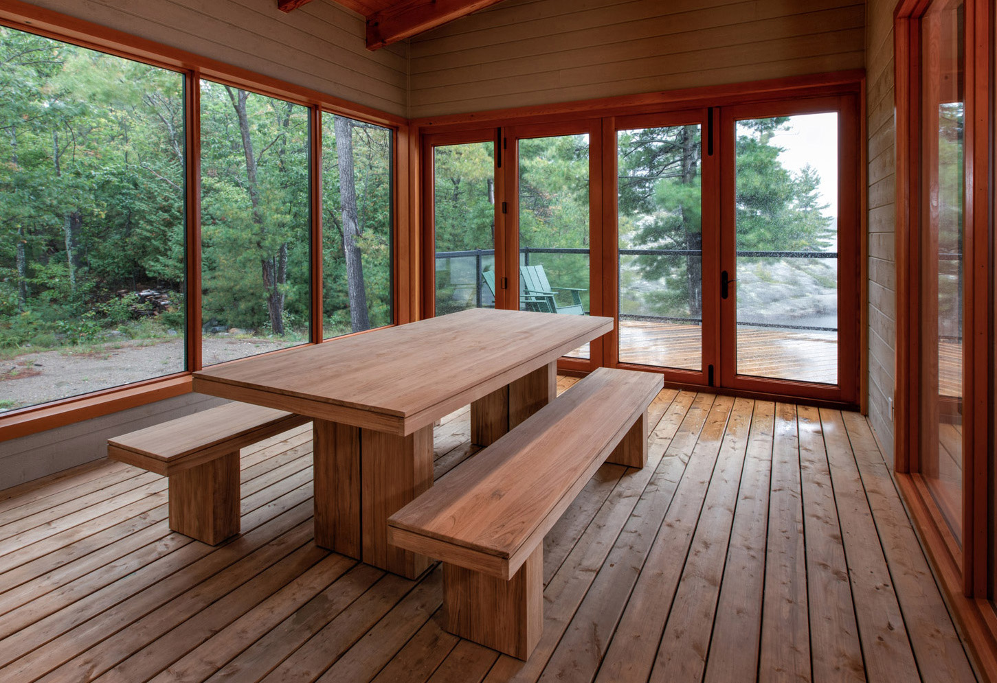 Exterior sunroom-with dining room table. Large modern table with bench seating, wrap around Douglas Fir windows and Kebony decking