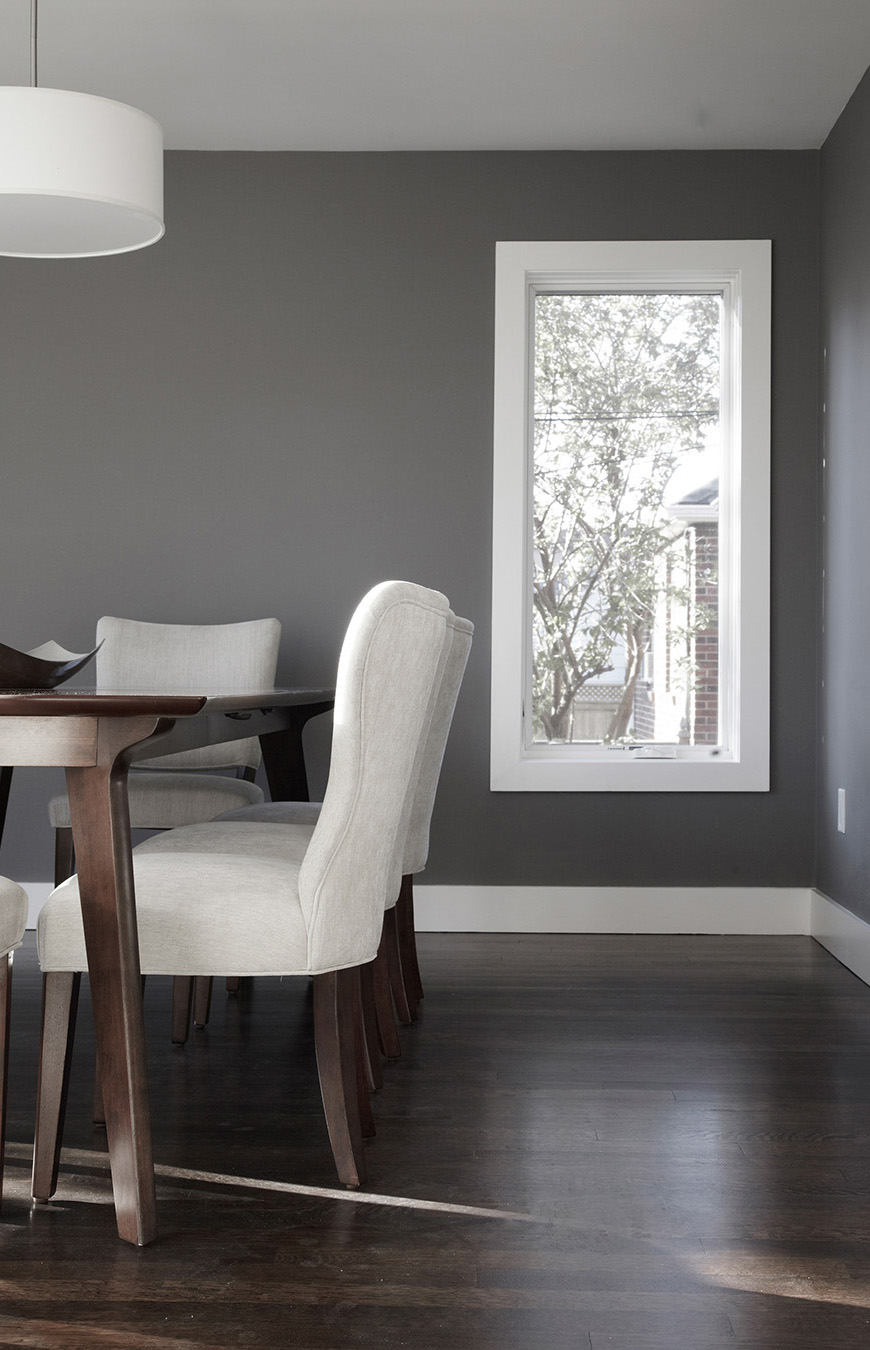 Modern dining room with modern wood dining room set with upholstered seating with white trim and gray walls