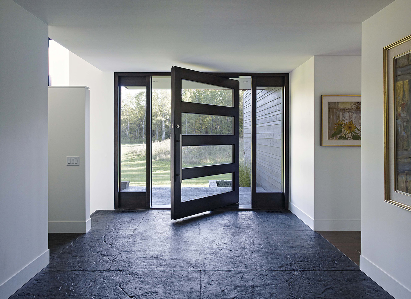 Modern home entryway with offset pivot door with double sidelights. Natural stone floor tile on exterior and interior