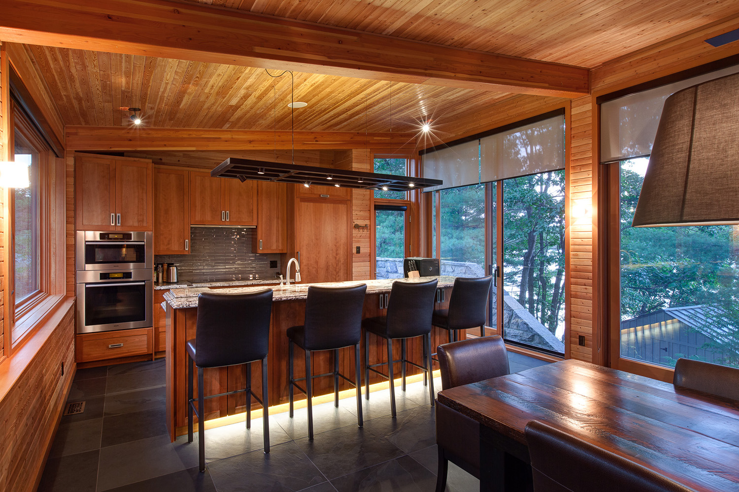 Open kitchen and dining room in Ontario cottage with large slate tiles, recessed lighting and custom wood cabinetry
