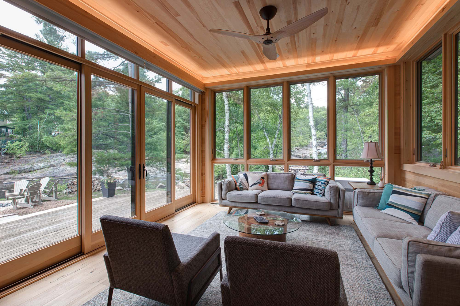 Cottage sunroom with wrap around wood frame windows and casement windows with recessed valance light