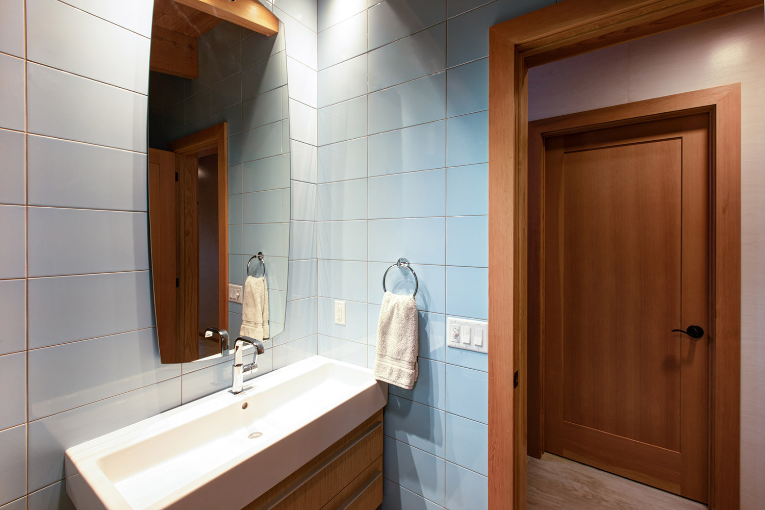 Bathroom with light-blue subway tile, Douglas fir door trim, and cantilever vanity with Basin sink