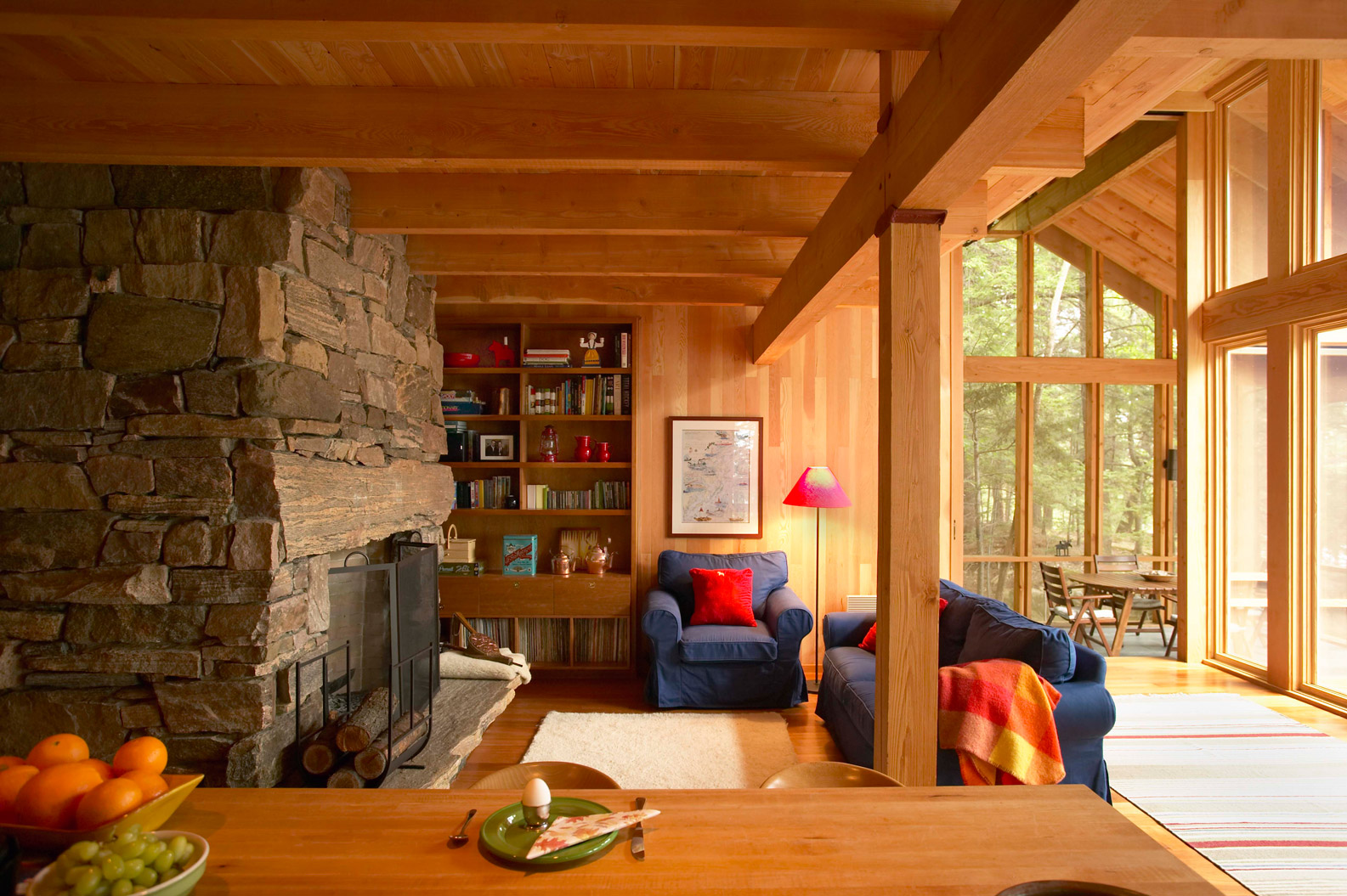 Timber-framed living room in Muskoka cottage with rustic granite fireplace and built-in bookshelves