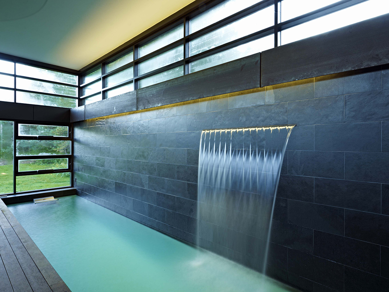 Indoor lap pool with Waterfall water circulator. Ipe pool decking and slate tile backsplash with recessed valance lighting