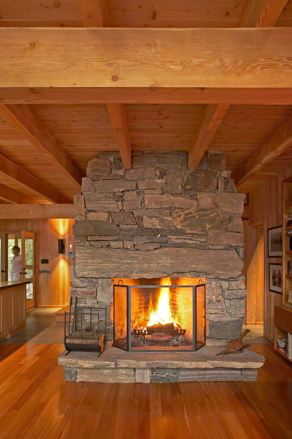 Rustic granite wood-burning fireplace in a timber-framed Muskoka living room.