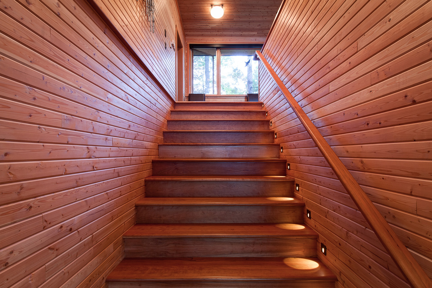 Wood cottage staircase with Step lights and wood handrail. V-channel tongue and groove pine walls