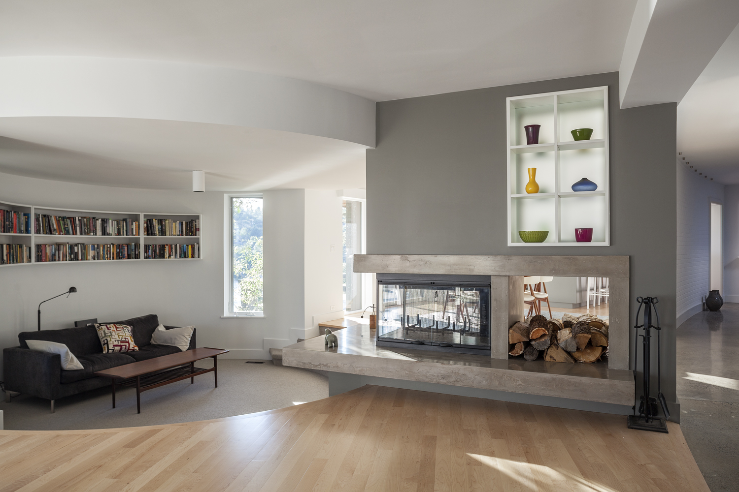 Recessed reading area with 3 sided concrete fireplace and backlit shelving and wood storage