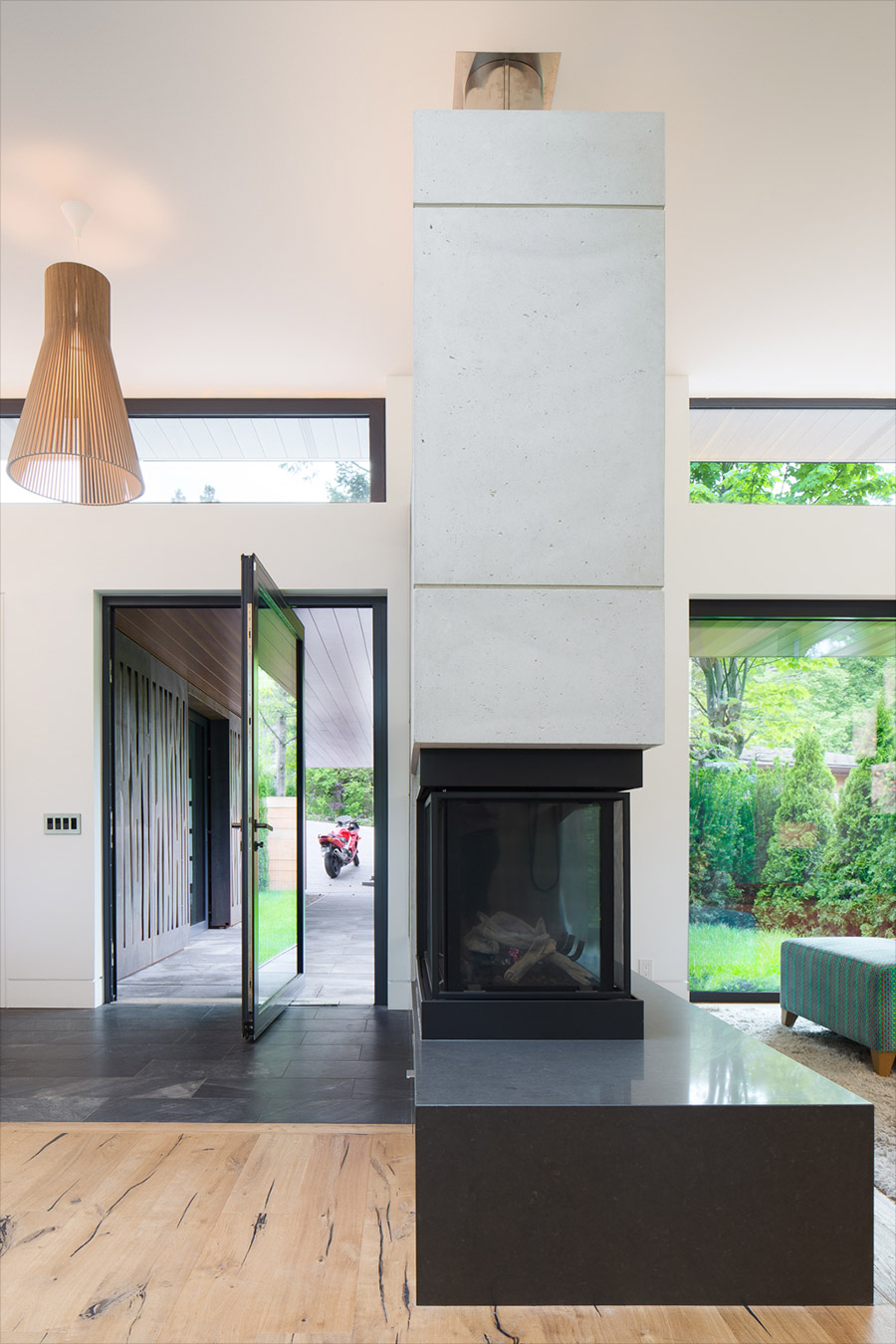 Toronto modern home entryway with offset pivot door and 3 sided fireplace divider between entrance and living room