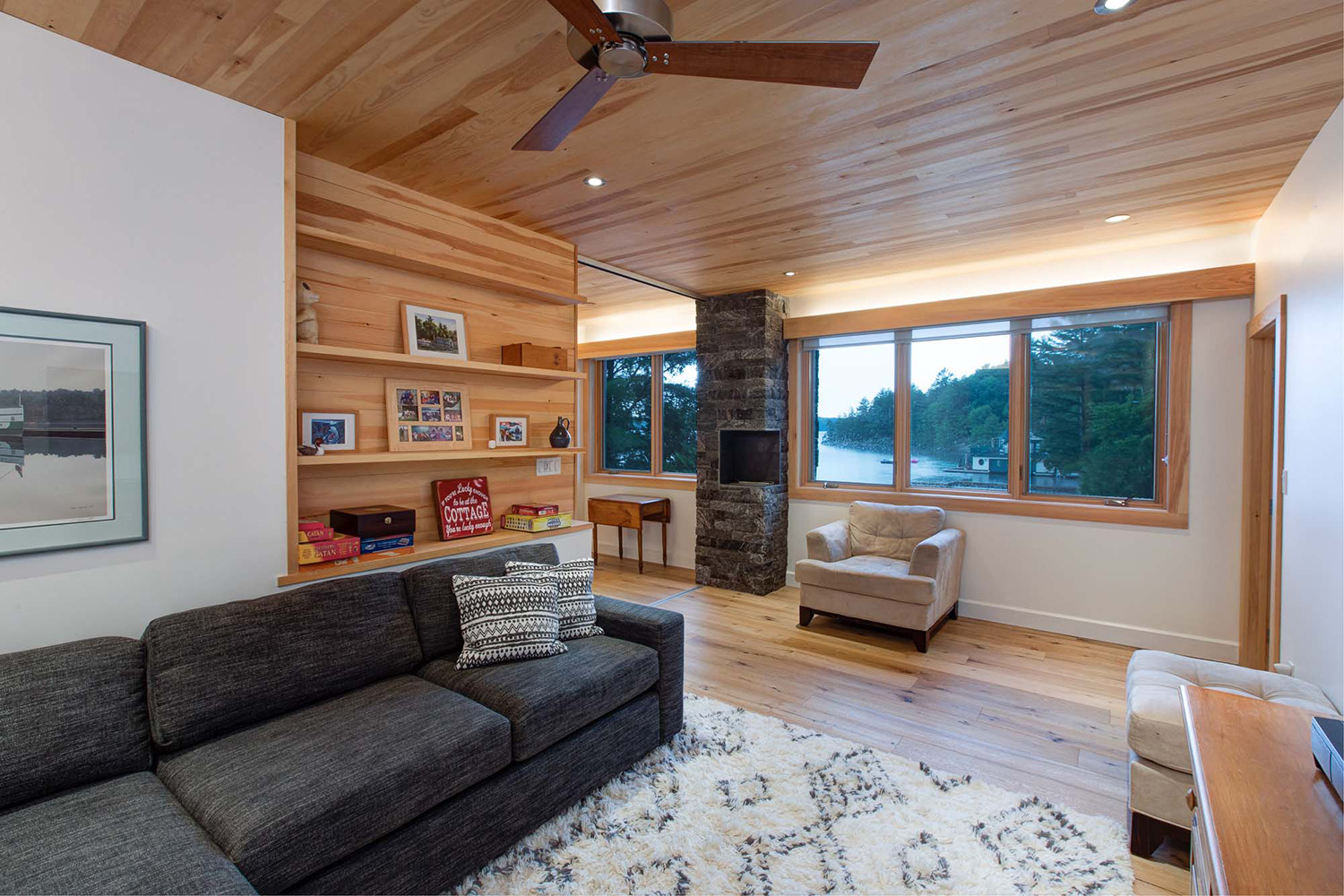 Canadian cottage siting room with built in clear pine shelving and modern gray sectional couch