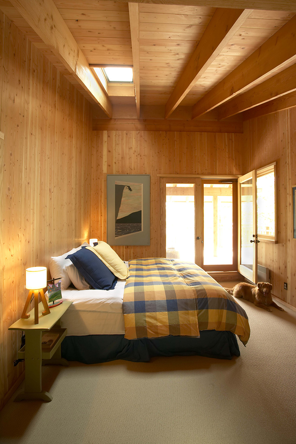 Timber-framed wood-clad bedroom with skylight.