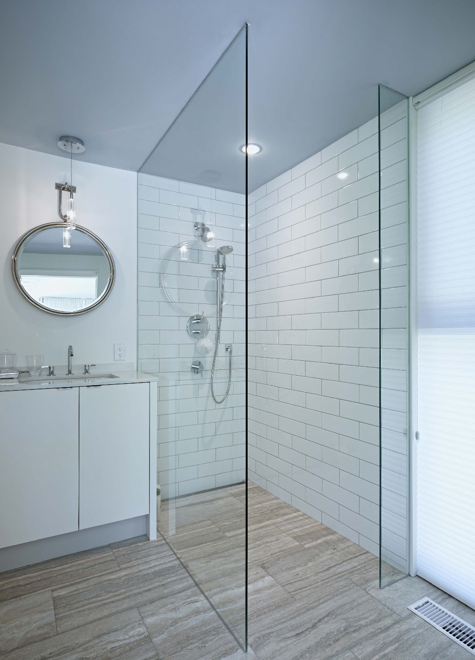 Bathroom with frameless glass shower and subway tile backsplash, with travertine stone tile floors