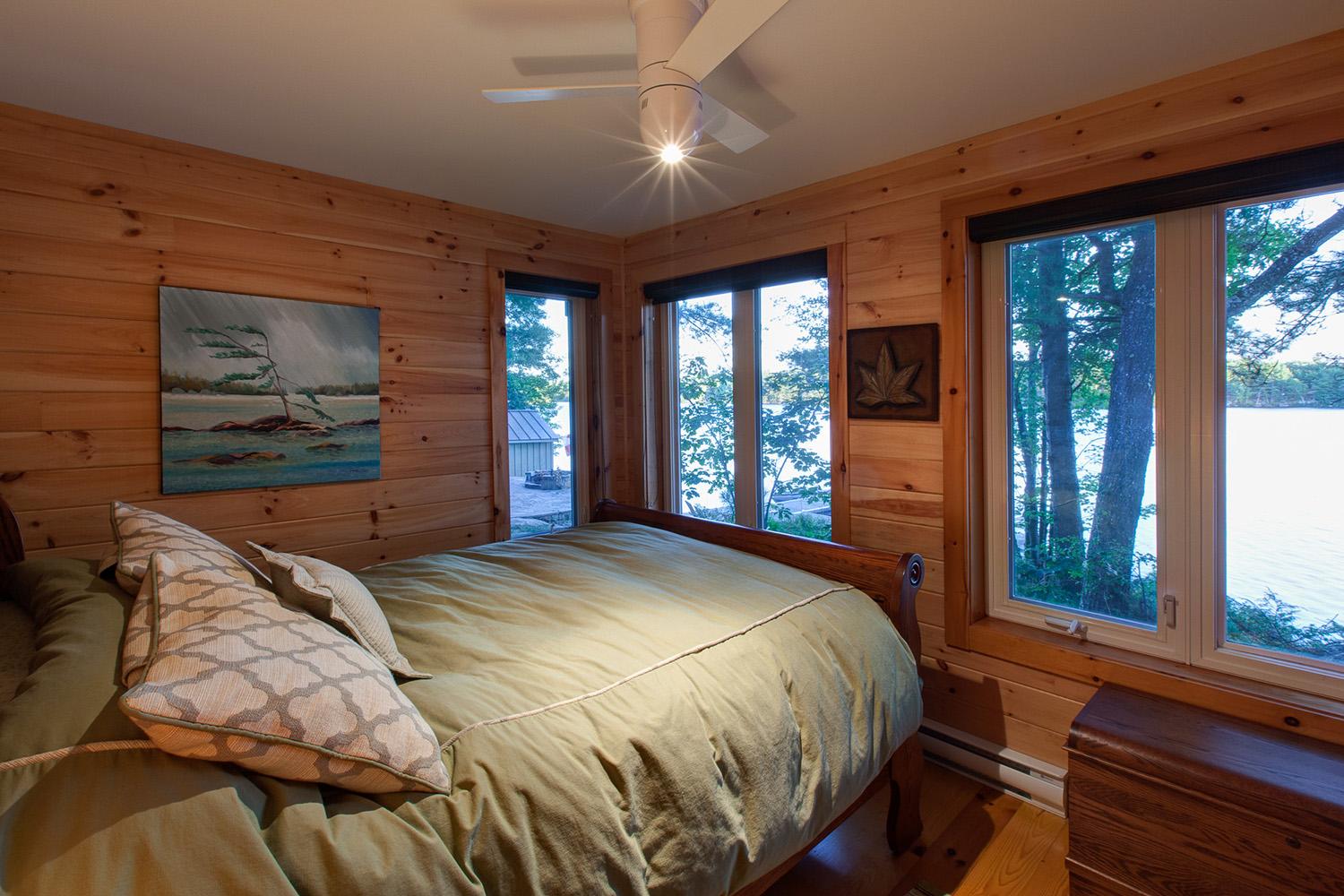 Guest bedroom with wrap around windows and view to the lake. Contemporary 3 bladed ceiling fan with light fixture