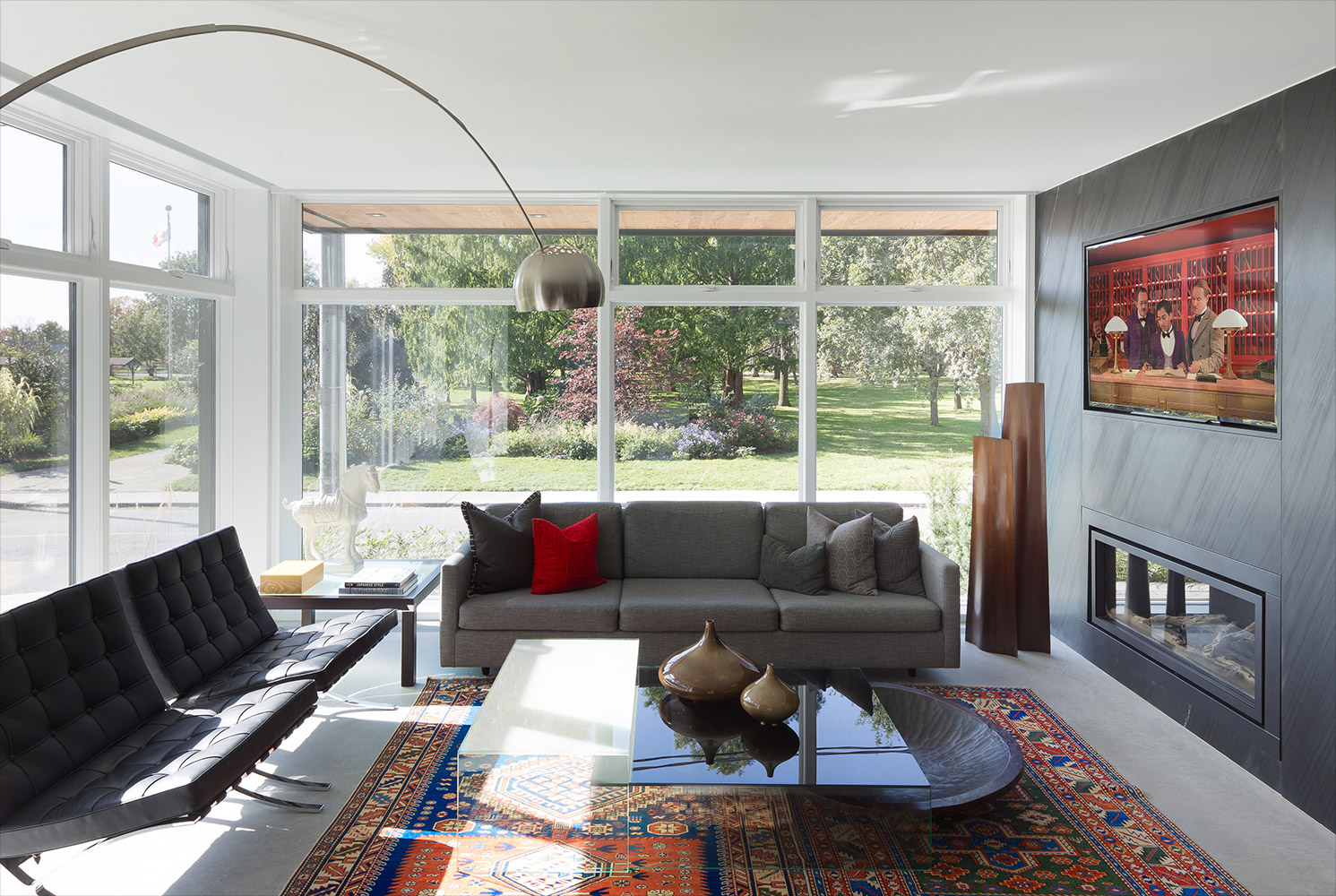 First floor living room with ribbon fireplace with textured black tile, polished concrete floor, floor-to-ceiling windows and gray sofa with Barcelona chairs