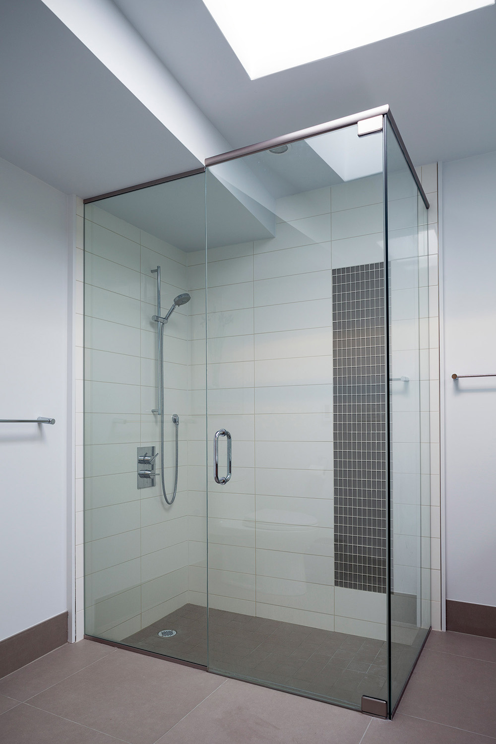 Recessed shower with glass enclosure subway tile backsplash with black accent tile strip and stainless steel fixture