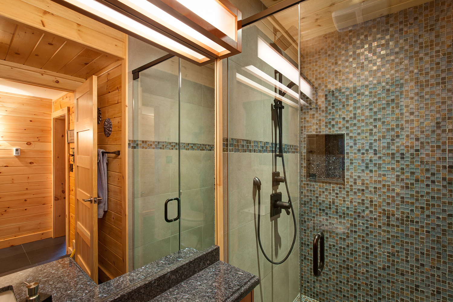 Bathroom with accent collage tiles, and integral shelf. Glass shower enclosure with anodized black fixtures