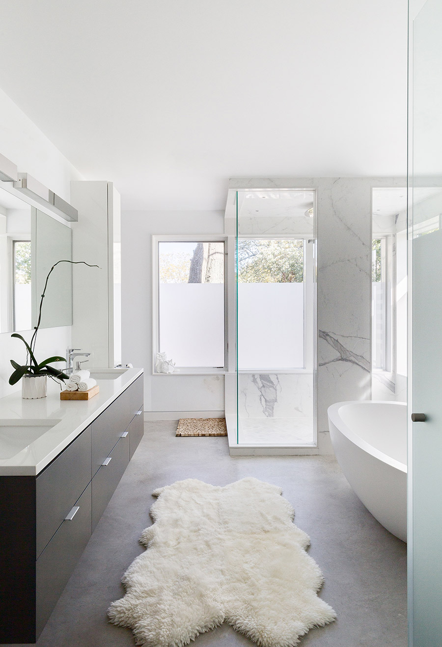 Bathroom with polished concrete floor and marble wall tiling, freestanding porcelain tub, and glass shower enclosure