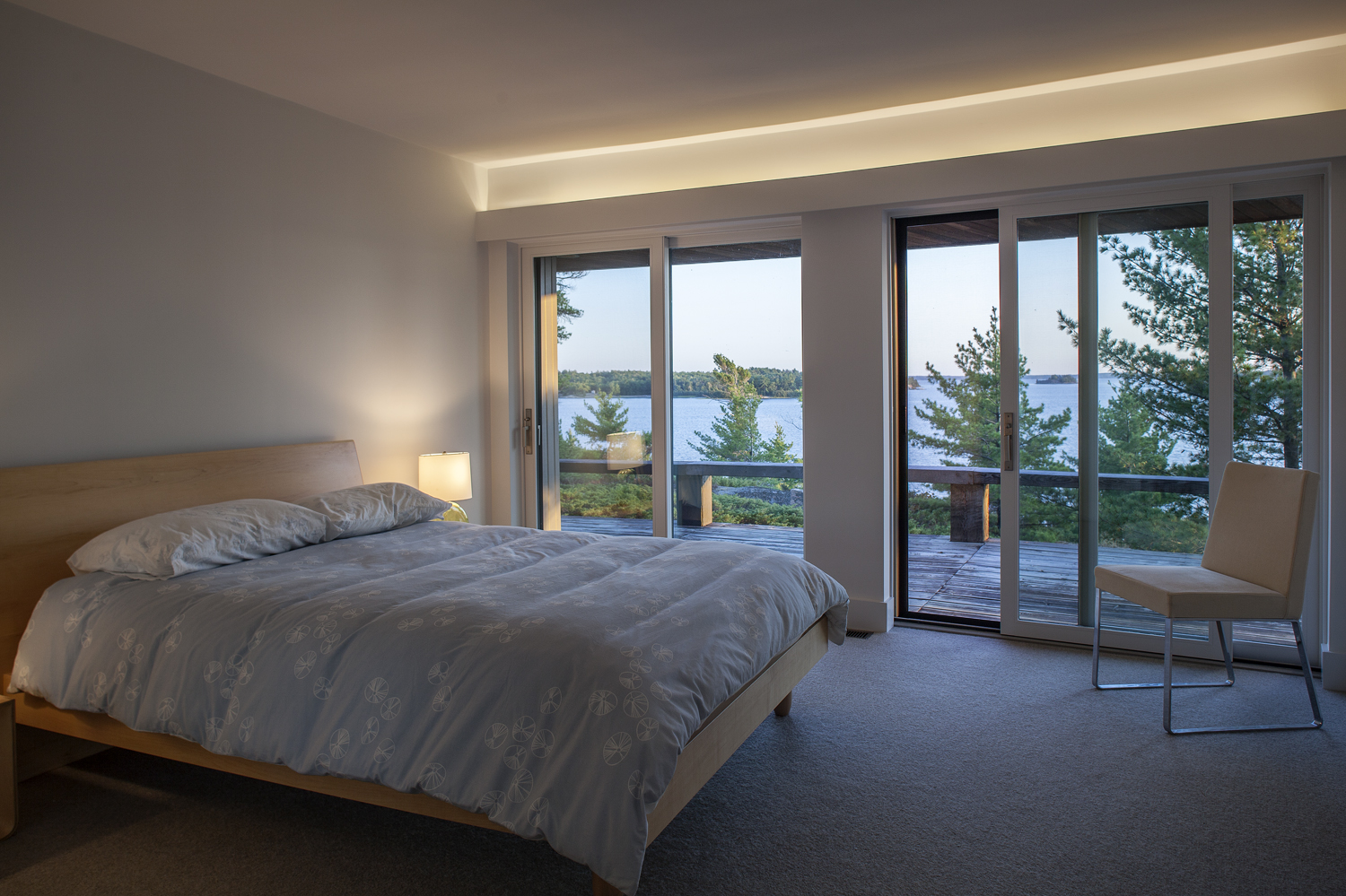Bedroom with contemporary Maple wood bedframe, recessed light valance, and walkout to balcony with view of Georgian Bay
