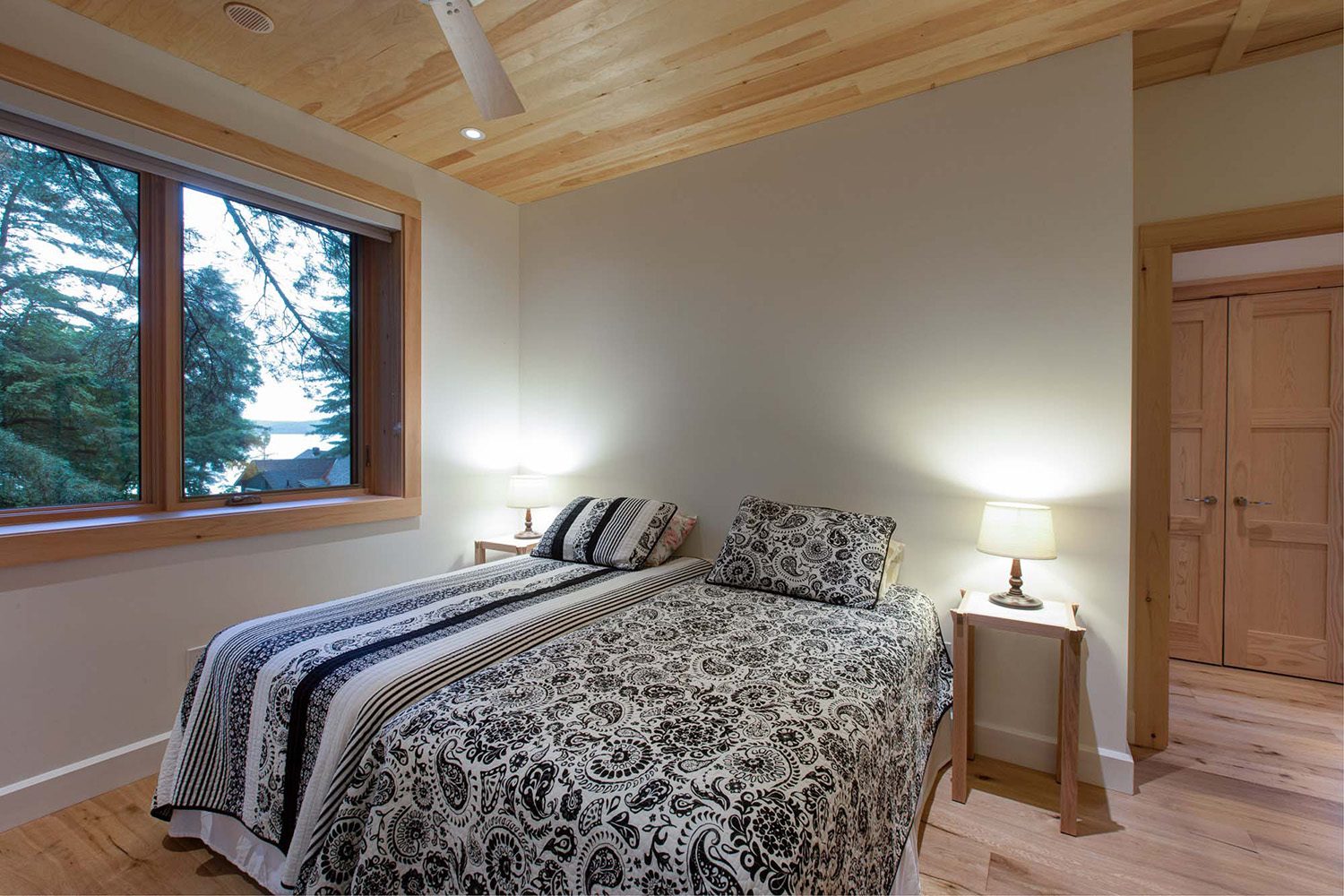 Cottage guest bedroom with modern decor and naturally finished wood ceilings and door and window trim
