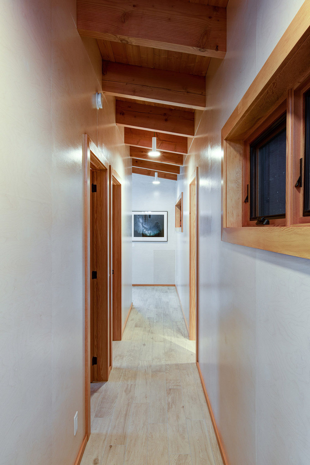 Cottage hallway with whitewashed birch plywood walls, and Douglas fir roof rafters and ceiling