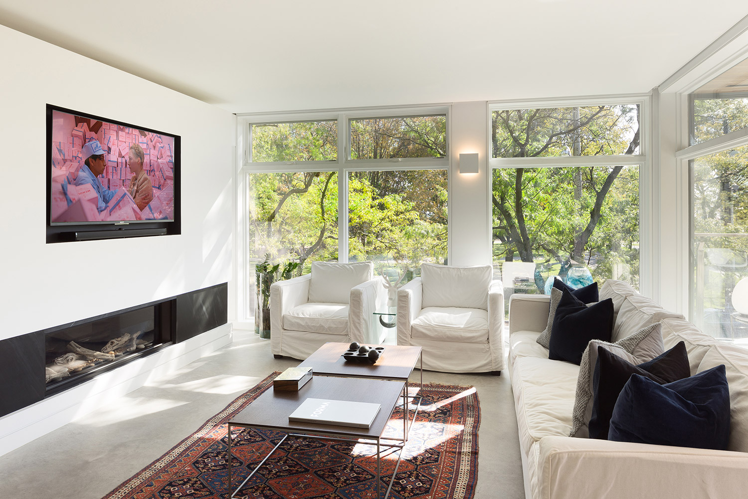 Second floor living room with ribbon fireplace and floor-to-ceiling windows with white couch and chairs